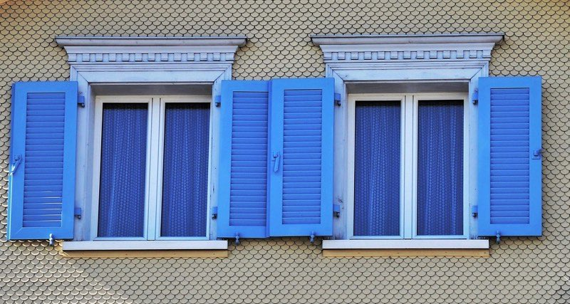 Blue curtains on windows with blue shutters