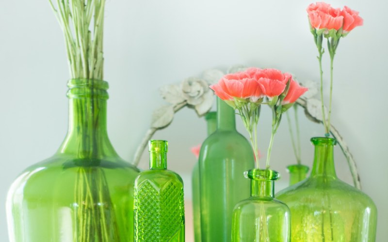 Green glass bottles with coral carnations