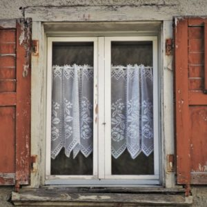 White lace curtains on a run-down old window
