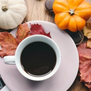 Leaves on a table with coffee and autumn pumpkins