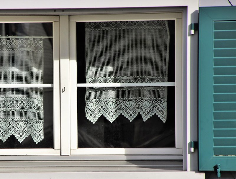 White window frame with teal shutters and lace curtains