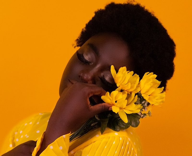 Pretty woman holding yellow flowers on her shoulder
