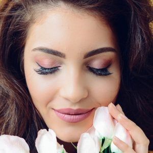 Woman with makeup smelling flowers