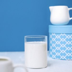 Glass with milk and a small white jug on blue background