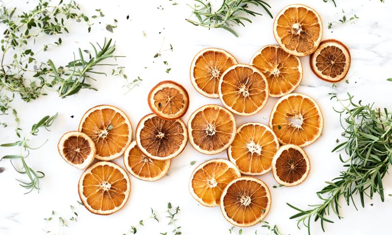 Slices of orange with herbs scattered on a table