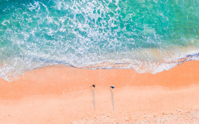 Photo of sand and sea taken from a drone