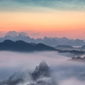 Sunset behind mountains with mist