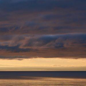 Dark rain clouds across a water body, probably ocean