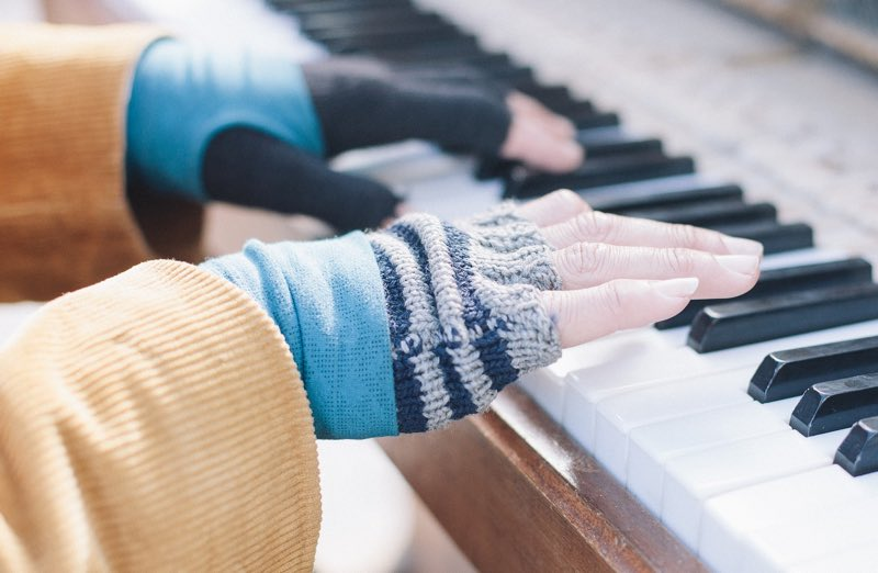 Hands playing the piano on a winter day